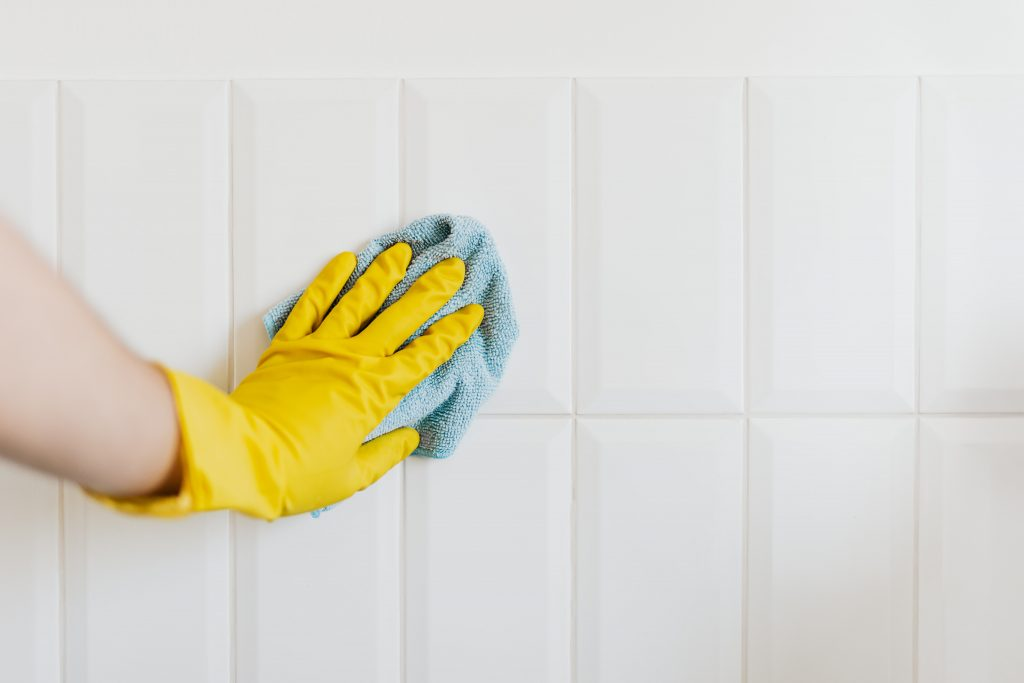 Crop person cleaning tiles with rag